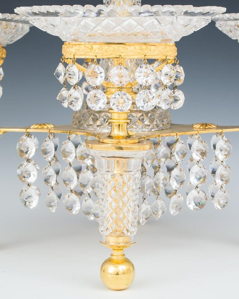 A fine ormolu and cut glass epergne by John Blades on four ball feet mounted with diamond cut tapered columns supporting a decorative drop hung plate, this issuing four drop hung ormolu baskets with oak leaf band supporting oval glass dishes cut