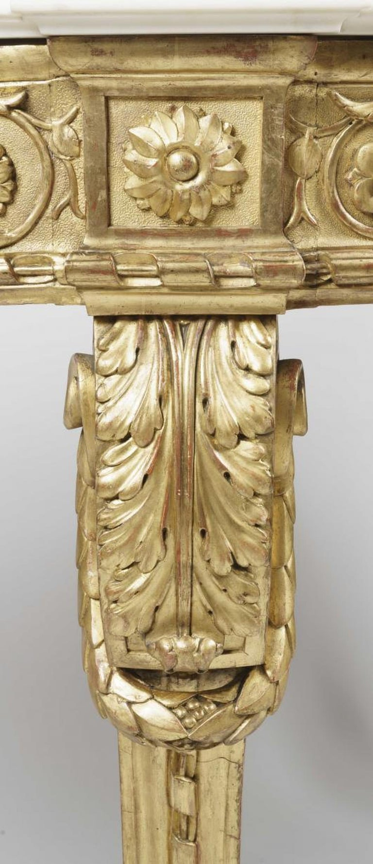 A fine pair of console tables in the Louis XV Manner  Constructed in carved and gilded wood; rising from four swept and scrolled legs adorned with acanthus designs, and dressed with looped garlands, and having conjoining stylised 'X' form stretchers