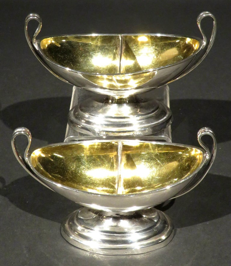 A very elegant pair of neoclassical inspired silver double salt cellars of navette form, both rising to swept open handles and having richly gilded and divided interiors, raised overall upon an oval foot bearing town marks for Leipzig, including