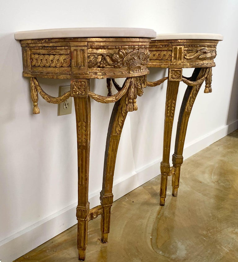 A fine pair of small Louis XVI  Carved giltwood console tables  18th century  Each with a D-shape white Carrara marble top,  above the guilloche-carved frieze, one centered by a woven basket flanked by fruit, the other with a sheaf of arrows.  Both