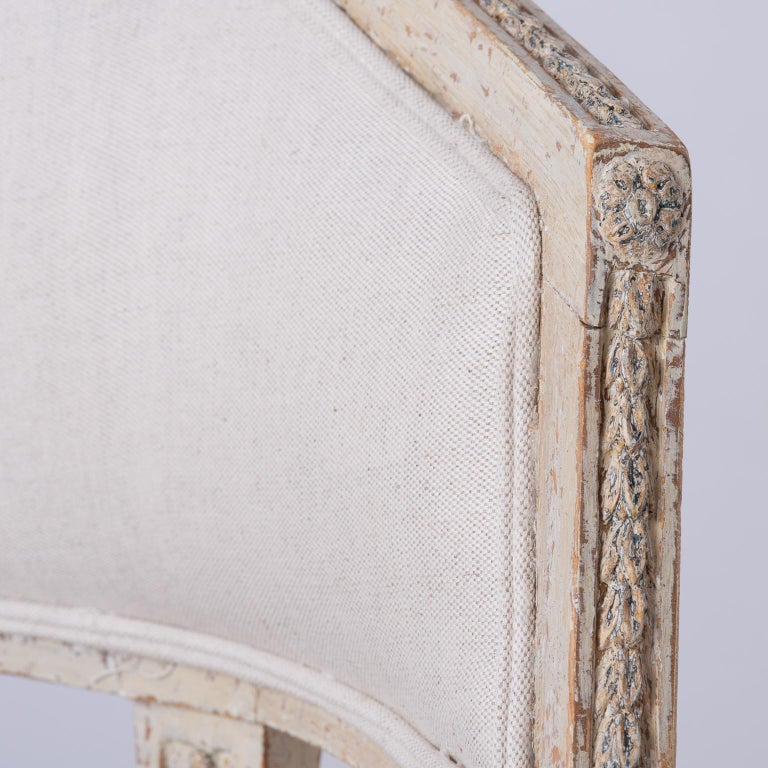 These high quality period chairs have delicate carvings across the back, accented with a flower medallion at the corners. The same motif is repeated on the apron and sides. The reeded acanthus legs have the added detail of a raised collar at the top