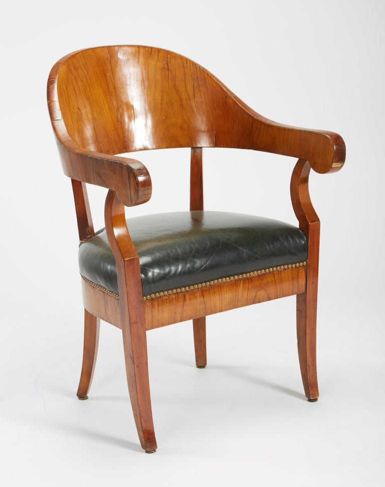 A fine set of six Austro-Hungarian Biedermeier fruitwood chairs, early 19th century, including an associated armchair, each sidechair with a crescent-shaped crest rail outlined in ebony, the verde antico and parcel gilt splat carved with a torch