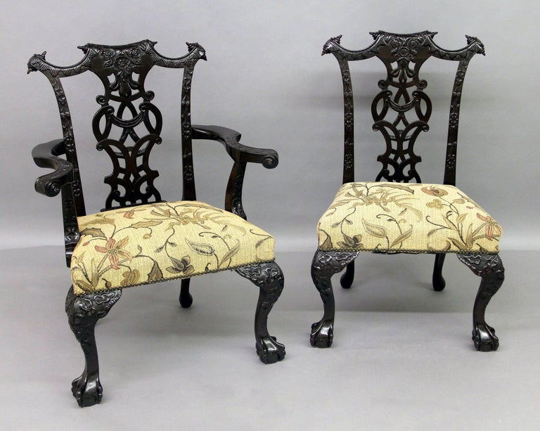 A fine set of ten late 19th century Chippendale style dining chairs  Comprising of two arm and eight side chairs.  The intertwined backs carved with roses and beautiful foliate designs, the top corners with paper scrolls. The serpentine arms