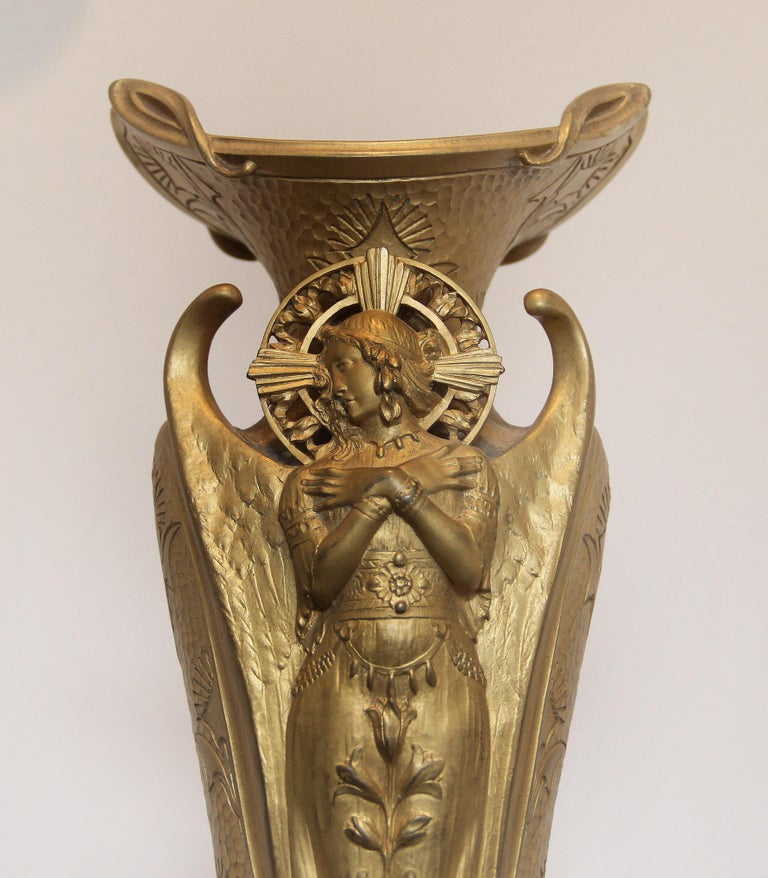 A fine turn of the century Art Nouveau gilt bronze vase or centerpiece  Bronze fluted body depicting an angel with wings and a halo, facing sideways with arms crossed. Nicely designed sides and back.  Signed Kery and stamped Colin on the base.