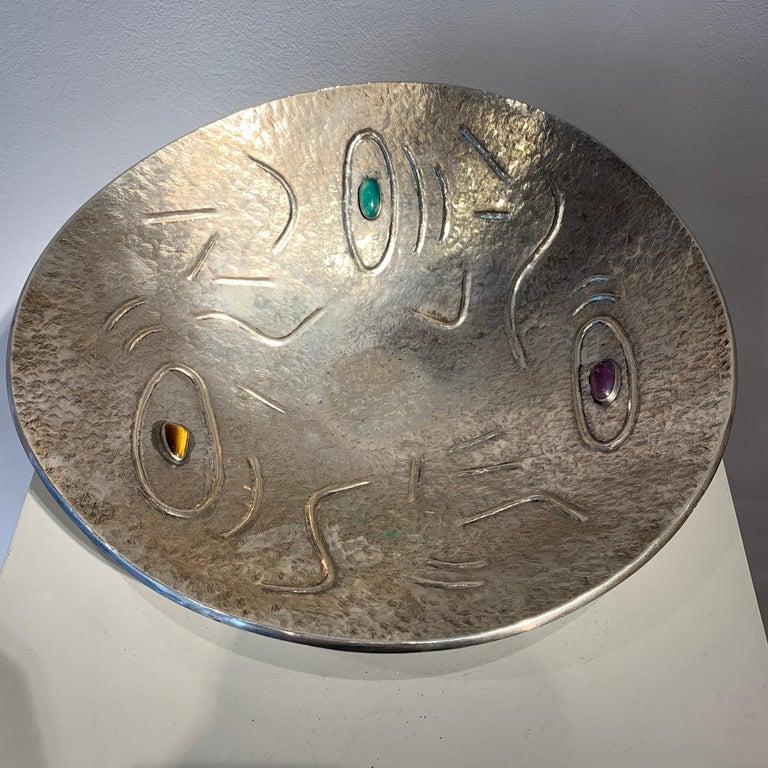 Finzi is a famous Italian Goldsmith. Typical of his work is silver objects with stones inserted. The design of this bowl shows an abstract decorative pattern.