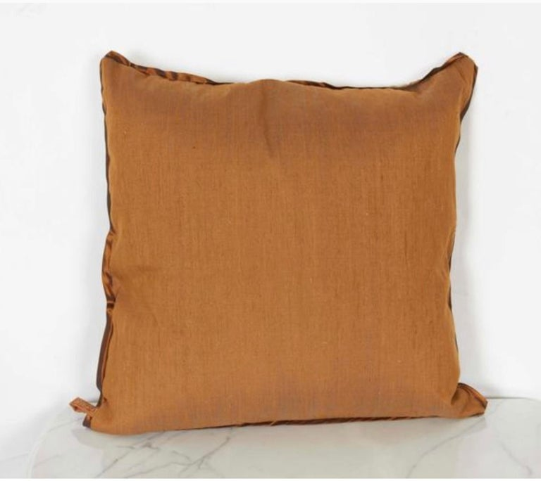 A Fortuny fabric cushion in the Impero pattern, copper and silvery gold color way with silk blend backing material and taffeta edging, the pattern, a 19th century French design with formal Empire motif. Newly made using vintage Fortuny fabric, circa
