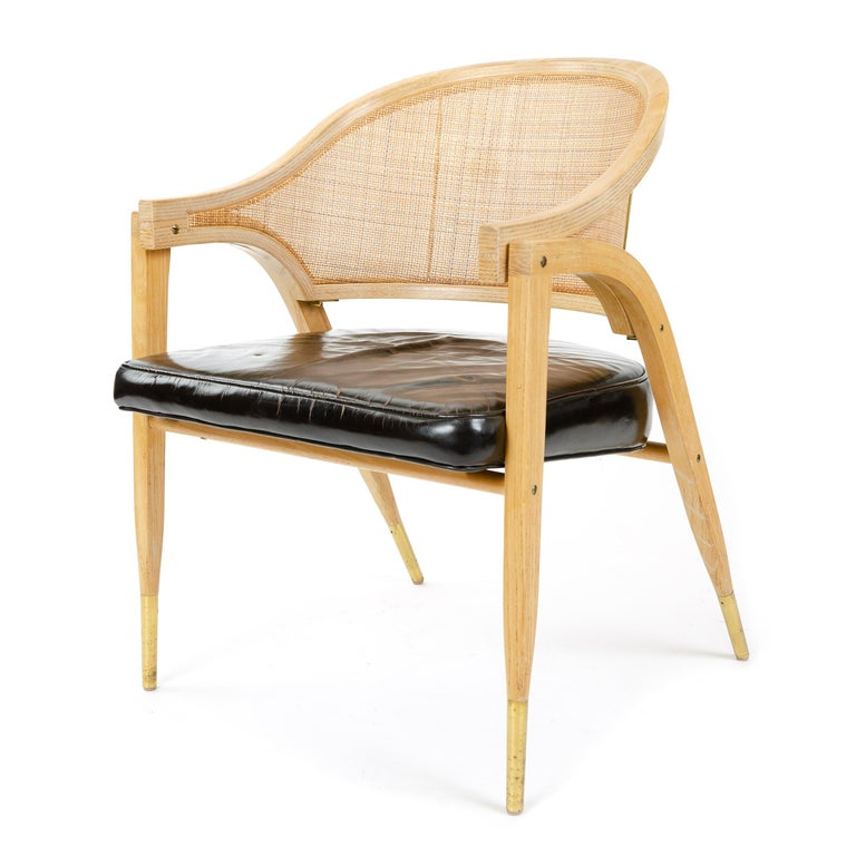 A Mid-Century Modern Classic 'A-Frame' armchair with a woven caned backrest, upholstered black leather seat and brass capped feet. Designed by Edward Wormley, produced by Dunbar in the USA, 1960s.
