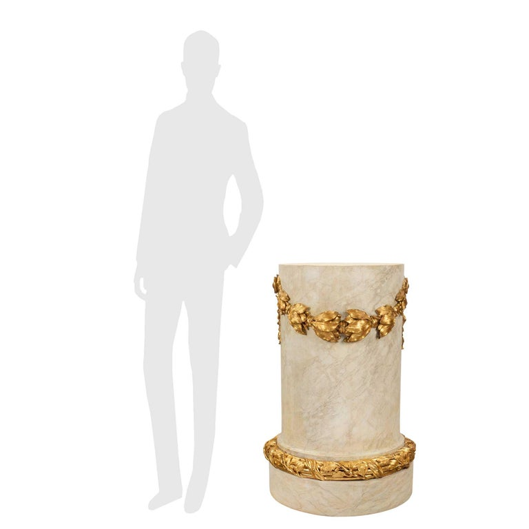 A beautiful and most decorative French 18th century Louis XVI period patinated faux painted marble and giltwood pedestal column. The column is raised by a circular base with a finely carved tied reeded giltwood band with elegant berried laurel