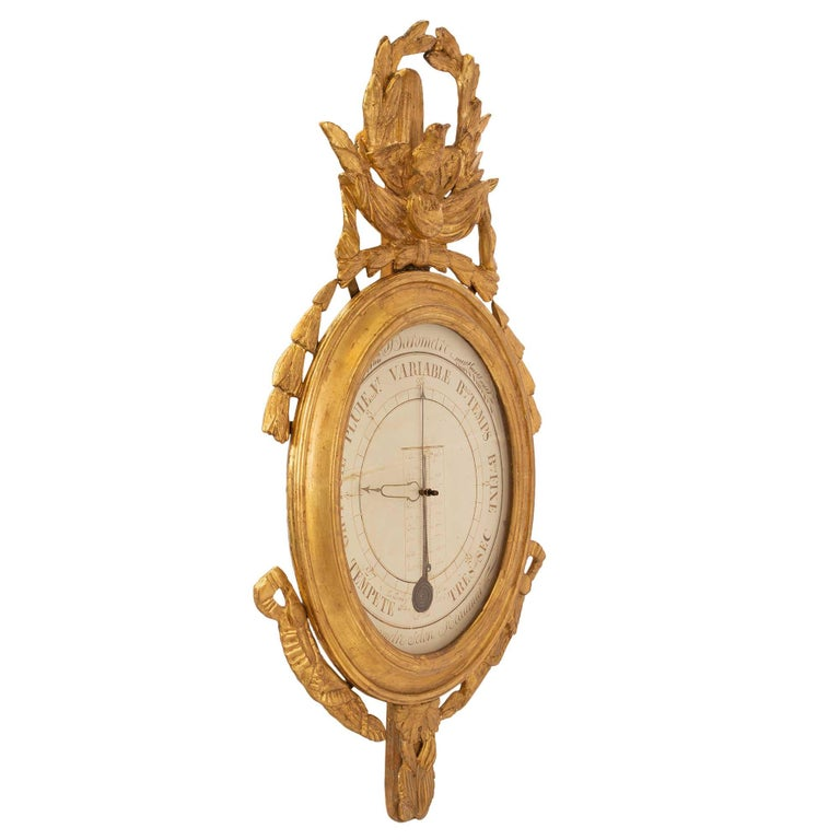 A very handsome French 18th century Louis XVI Period giltwood barometer and Réaumur thermometer. The hand painted dial is fitted with metal hands and framed within a mottled oval giltwood frame. The giltwood frame has a top pierced crown with a