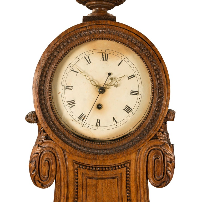 A handsome French 18th century Louis XVI period oak grandfather clock. The clock is raised by a square mottled base with an elegant carved recessed design. At the center is a finely carved acanthus leaf border below the circular glass display with