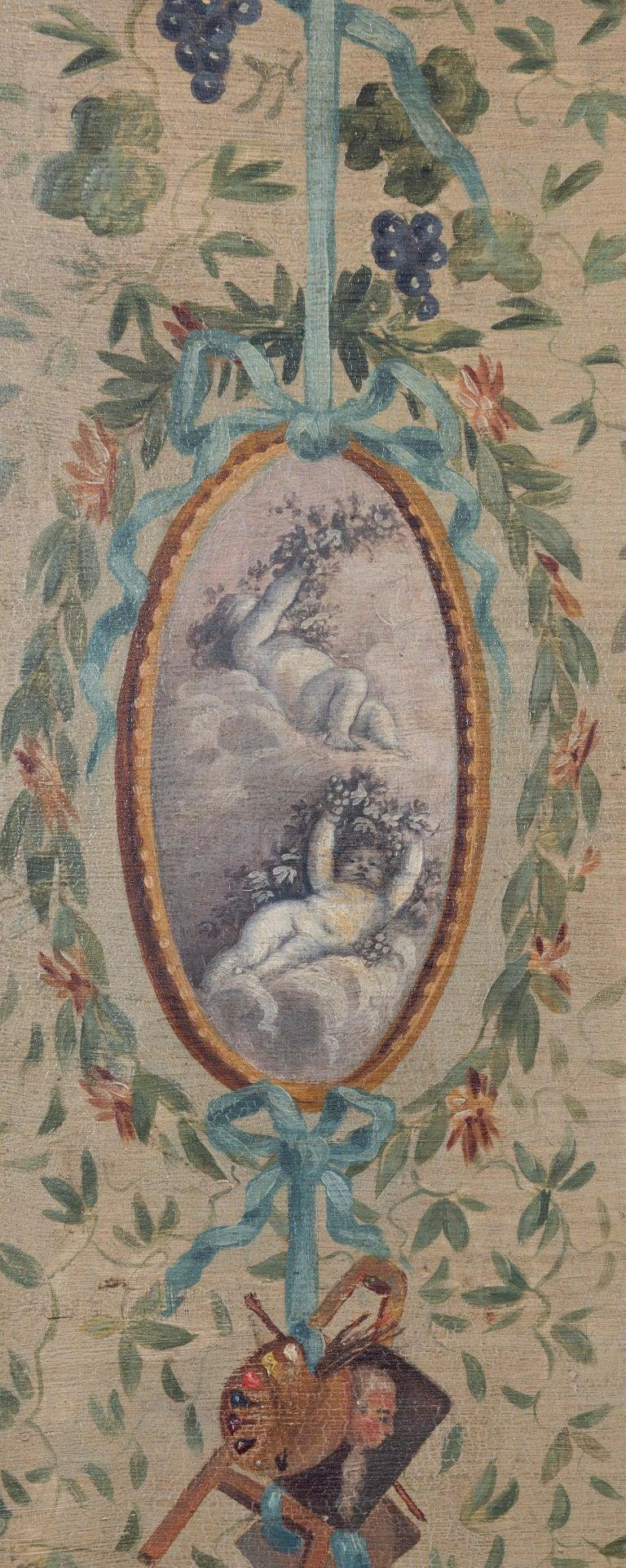 Each panel painted with classical oval shaped medallions depicting putti, surrounded by floral wreaths, musical trophies, foliage and ribbons on a pale olive green ground.
