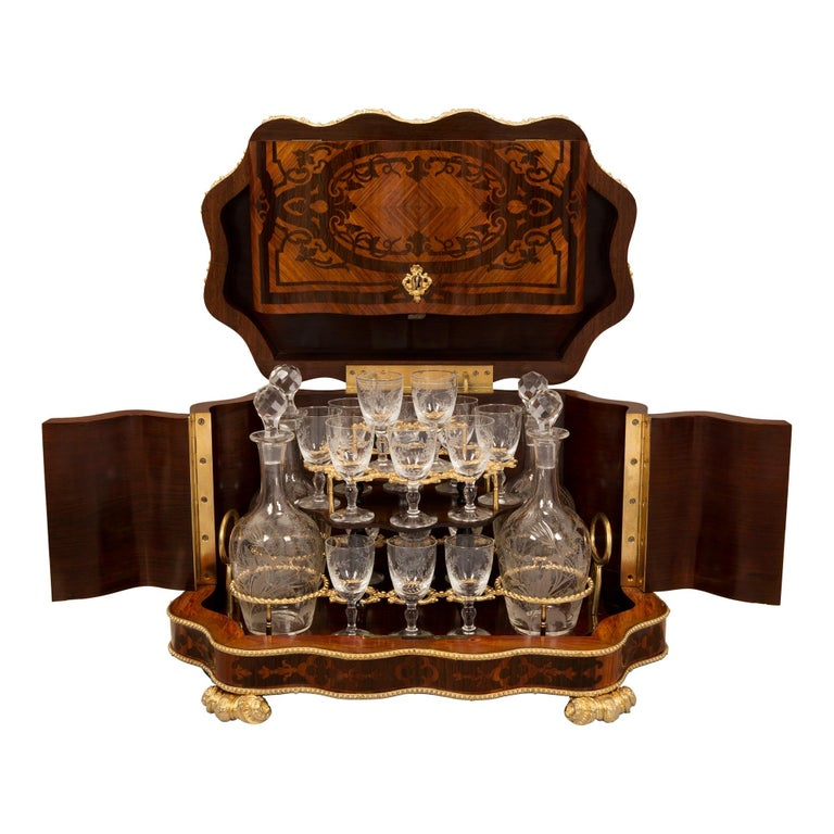 An exquisite French 19th century Louis XV style Kingwood, Tulipwood and ormolu cave a liqueur with its original etched crystal decanters and glasses. The cave a liqueur is raised by elegant scrolled wave like ormolu feet below the most decorative