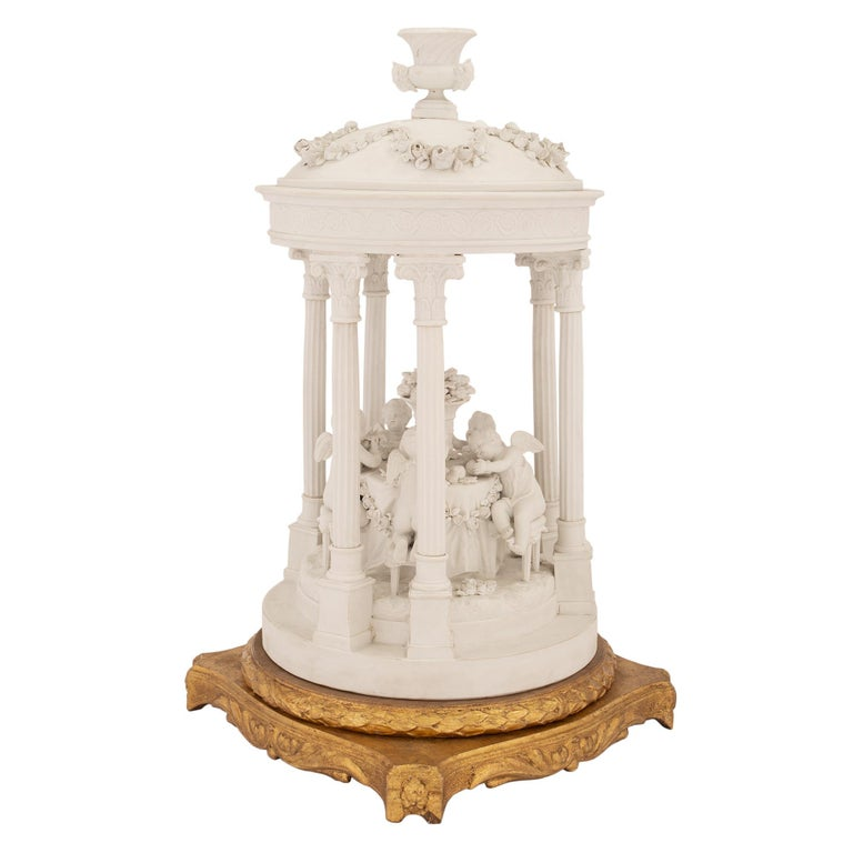 A sensational French mid-19th century Louis XVI st. Biscuit de Sèvres and giltwood centerpiece. The statue is raised by a richly detailed square giltwood base with slightly curved sides. Each side are decorated scrolled acanthus leaves below a fine