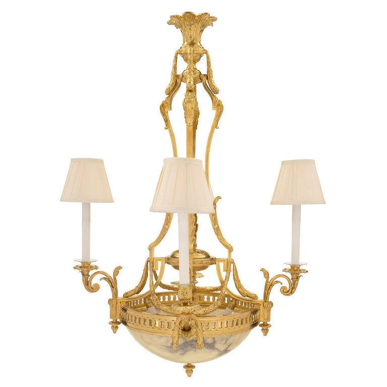 An exquisite French 19th century Louis XVI style ormolu and alabaster four arm, six light chandelier. The chandelier is centred by a charming bottom ormolu acorn finial below the striking alabaster bowl which houses two interior light bulbs offering