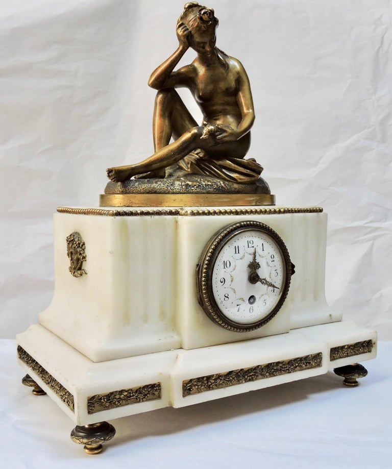 A French 19th century marble and ormolu clock  The Carrare marble case surmounted by a bronze sculpture after Etienne Maurice Falconnet,