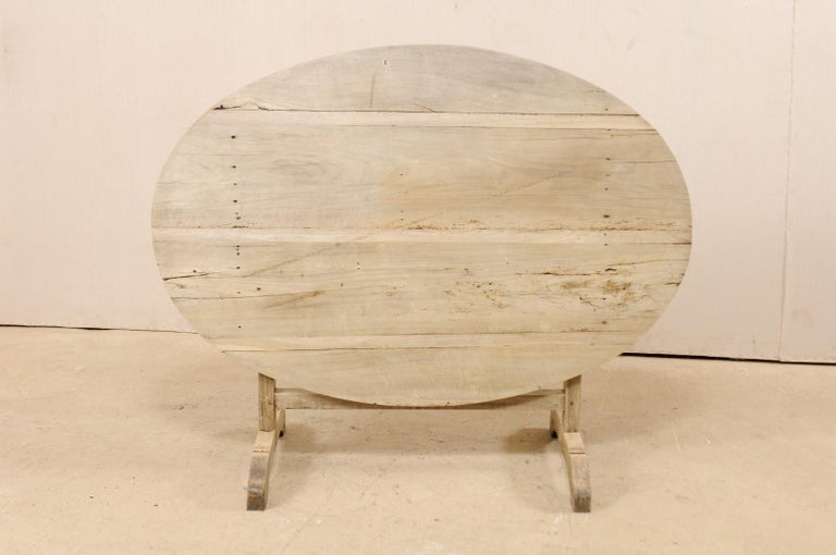 A French wine tasting table from the 19th century. This antique oval-shaped table from France features a tilt top, which is the signature of wine tasting tables during this time. When in use, the top is supported with a butterfly wedge, which turns
