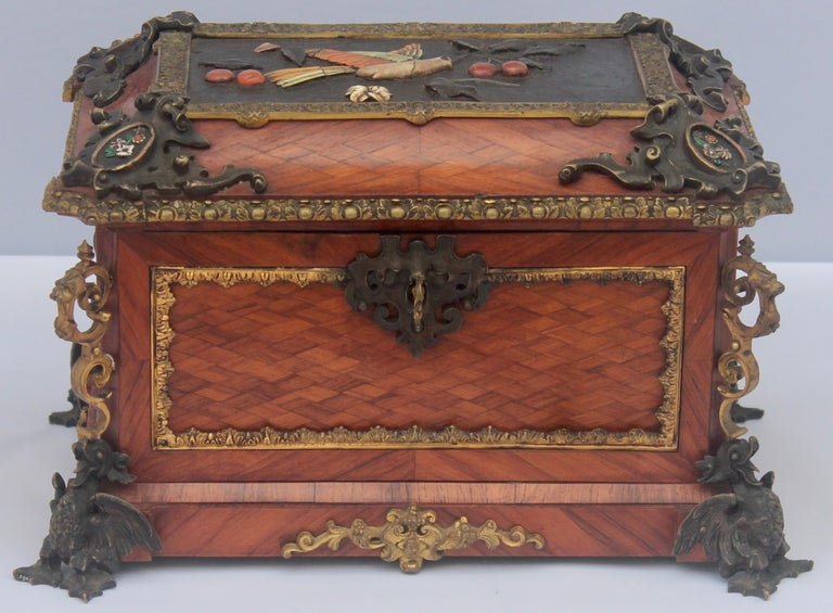 """A French 19th century Jewelry Casket by Alphonse Giroux, Paris A """"chevron"""" motif wood veneer rectangular cassette , gilded and patinated bronze ornamentations, resting on four fantastic animals attacking. On the top, a Pietra Dura design of a"""