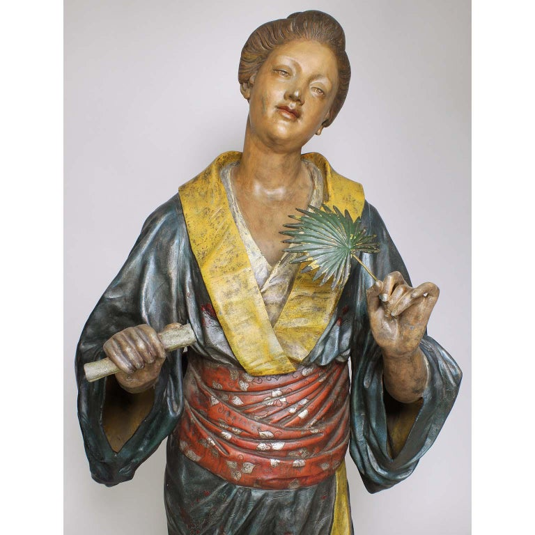 A fine French 19th century Polychromed Japonisme life-size cast-metal figure of a standing Geisha, cast after a model by Charles Massé (French, 1855-1913). The standing Japanese beauty wearing a flowing Kimono with both hands raised, holding a palm