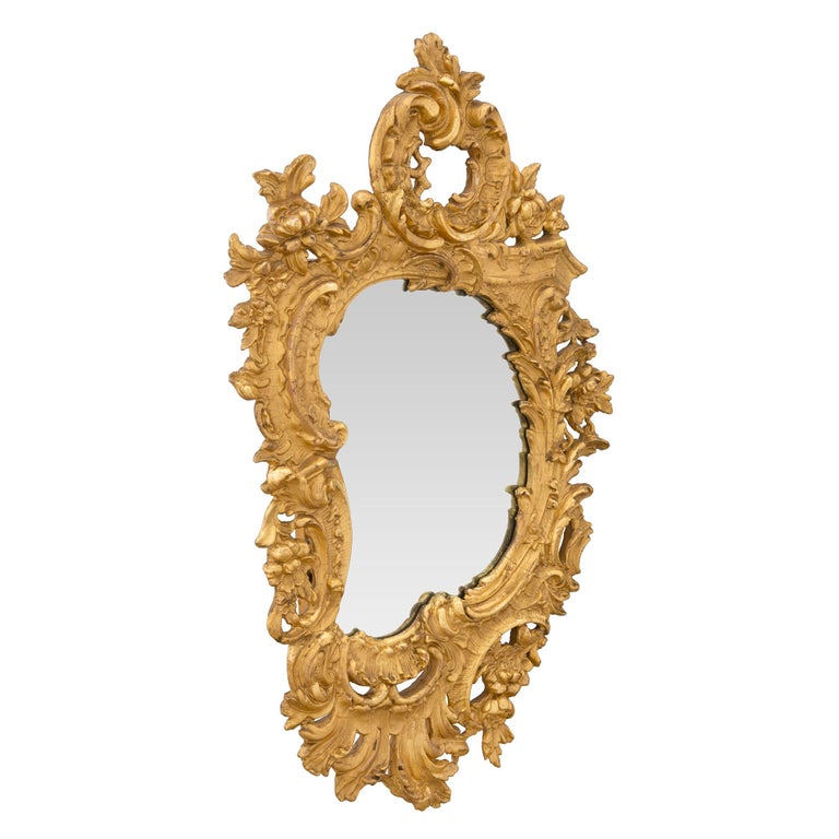 A handsome French 19th century Rococo st. giltwood mirror. The original mirror plate is framed within a striking asymmetrically shaped border. The mirror displays a stunning large pierced frame carved with scrolling foliate and floral garlands. The
