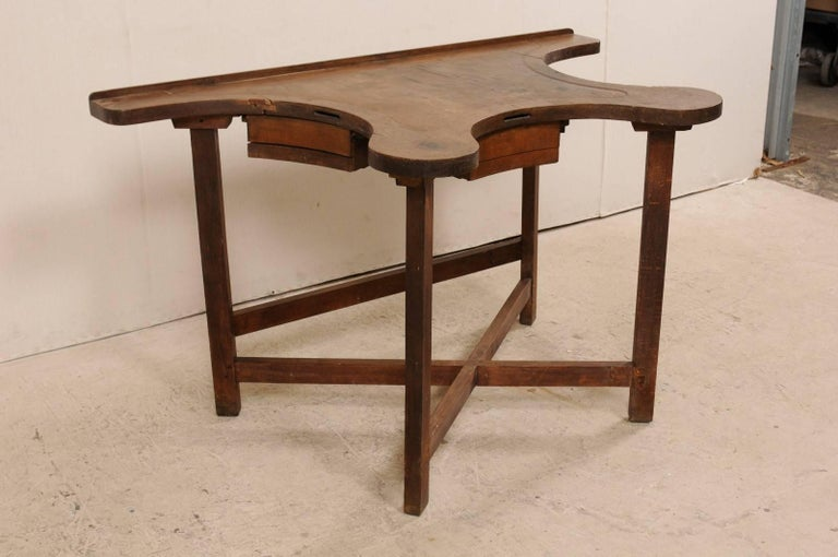 A French jeweler's work bench table from the early 19th century. This unusual French table was originally used during the early 19th century by a jewelry maker, a work bench for designing. The table features a flat back side with wavy, concave sides