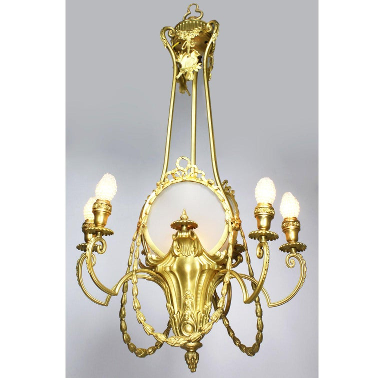 A French Belle Époqueneoclassical revival style gilt metal six-light chandelier. The open slender gilt metal frame with a single light central urn surmounted with three oval frames decorated with tied ribbons and suspended swagged floral wreaths
