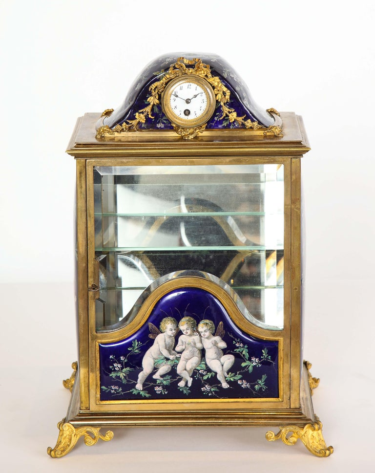 A french bronze and limoges enamel jewelry vitrine cabinet with clock, 19th century.  Hand-Painted with beautiful cobalt blue panels of cherubs. The door opening to glass shelves, and mirrored glass with original key.  The top, with an original