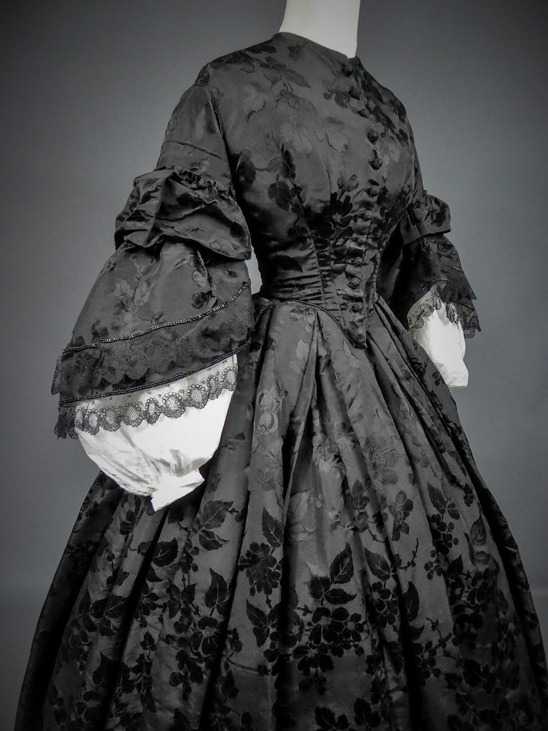 Circa 1862/1865 France  Mourning crinoline dress (bodice and skirt) in flowery damask silk faille dating from the end of the Second French Empire. Bodice and adjoining skirt in satin damask faille or Gros de Tour. Lined and boned bodice with large
