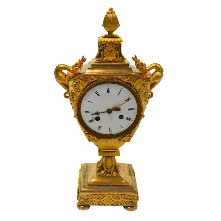 An are model French Empire mantle clock featuring a classical urn with dragon handles. The clock is entirely of gilded bronze with original fire gilding. The urn-shaped case is surmounted with a pineapple finial; on either side of the 4.5? White