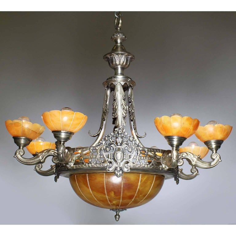 A French early 20th century Art Deco silvered bronze and carved caramel-color alabaster eight-light chandelier. The pierced silver plated bronze frame, suspended by four scrolled braces with acanthus decorations, surmounted by eight scrolled shaped