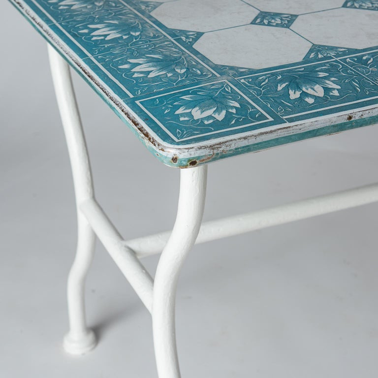 This charming table has an enamel top of blue and white flowers in a pattern of squares made to look like tiles. The base is made of white painted tubular metal. It was most probably part of the decor in a florist shop somewhere on the Cote D'azure,