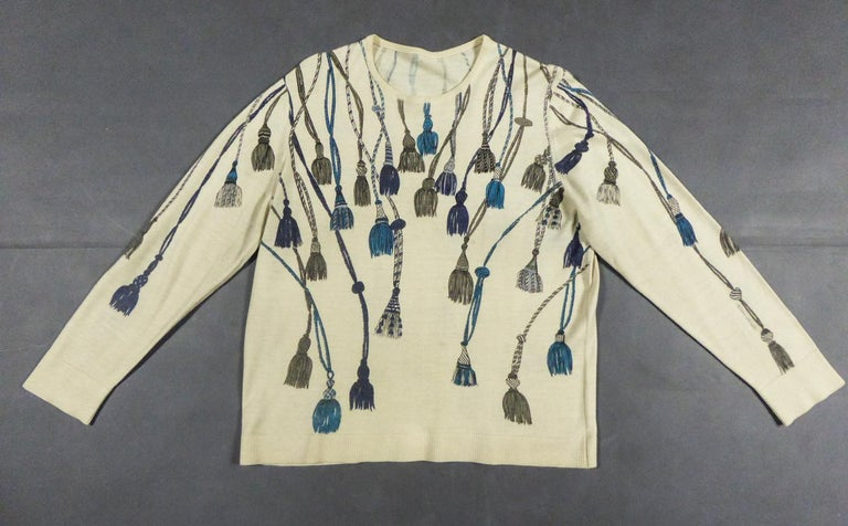 Circa 1960 France  Elegant sweater in fine wool and silk knitwear with a round neck and long sleeves from the famous house designer Henry à la Pensée and dating from the late 1960s. Cream background printed with tassels of trimmings, cords and
