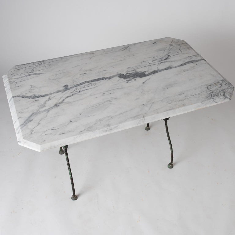 This table has a lovely green painted base retaining the original color and special details, with medallions at each side and pad feet. The large piece of marble with elaborate veining and beveled edges is quite attractive.