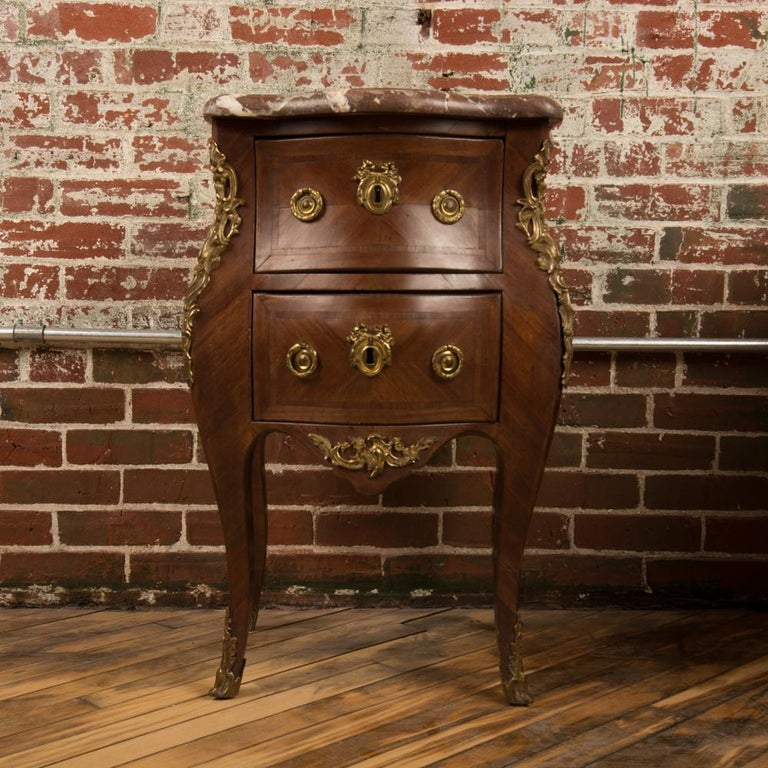 A French Louis XV style marquetry side cabinet, circa 1940. The nightstand features mahogany wood grain and a red beveled marble top. The nightstand offers two drawers, and the case rests on cabriole legs with mounted ormolu details.