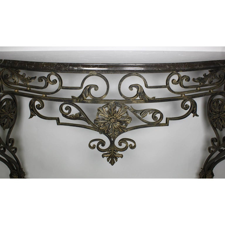 A Large French Louis XV style wrought iron wall mounting console with marble top. The ornately scrolled iron frame surmounted with floral decorations and fitted with a veined grey marble top, circa 20th century.
