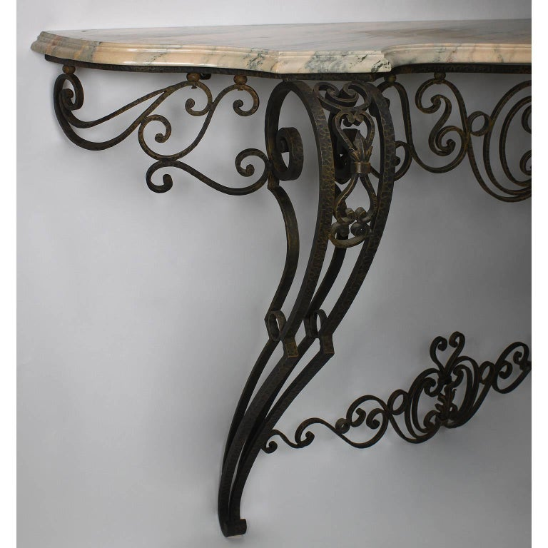 A French Louis XV style wrought iron wall-mounting console with marble-top. The scrolled serpentine iron frame with voluted front support legs with tapered feet, fitted with a veined pinkish color marble top, circa 20th century  Measures: Height