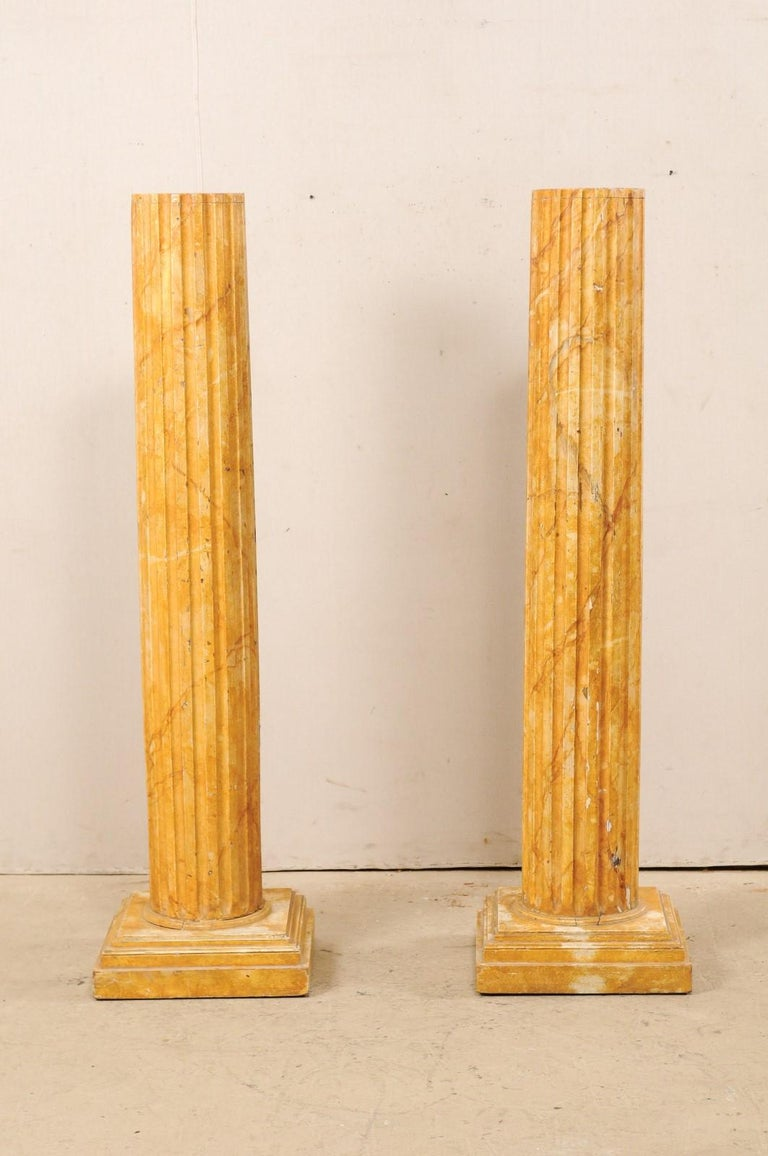 A pair of French fluted wood columns with faux marbling from the mid-20th century. These vintage pedestal columns from France feature round-shaped and fluted shafts, with a flat top, and raised upon stacked square bases. The columns have a faux