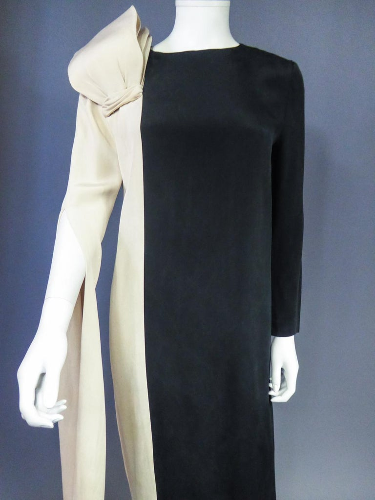 Circa 1975/1985 France  Astonishing evening Peplum dress in silk jersey playing with the bichromy of Yin and Yang, and signed by Pierre Cardin Prestige dating from the early 1980s. Funny nod to Yves Mathieu Saint Laurent at Dior in 1955 in the more