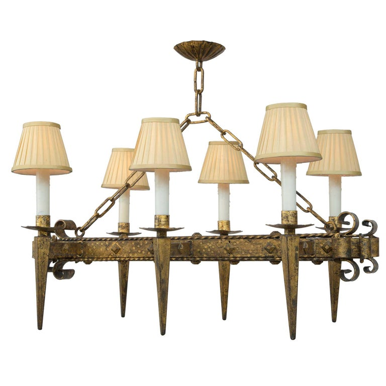 A handsome French Renaissance style 19th century gilt iron six-arm chandelier. The rectangular shaped chandelier has a square central hammered fut decorated by diamond shaped buttons and twisted ribbon edges. The two ends with wonderful and