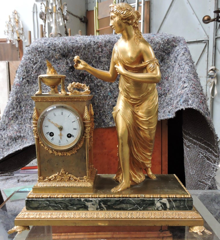 A French 19th century Restauration marble and ormolu mantel (fireplace) Clock,  Designed with a Vestale Woman watching the Vesta Temple Fire On a green