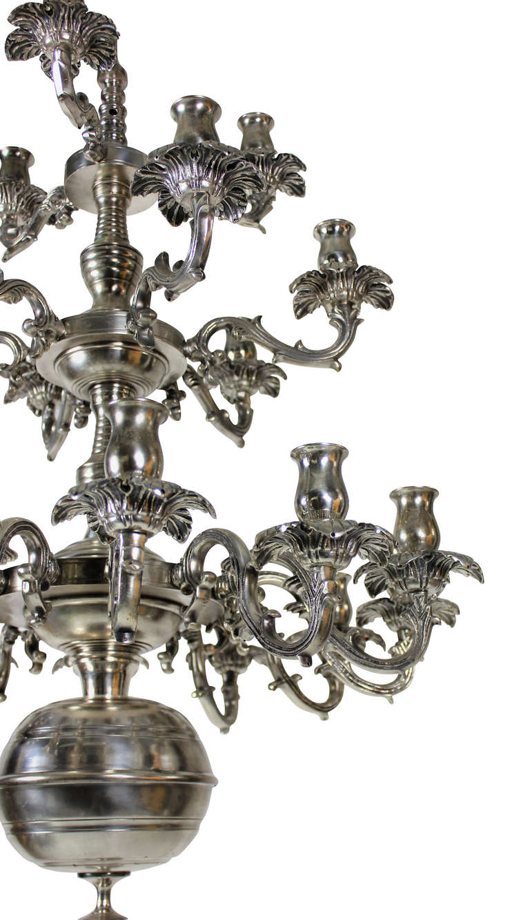 A large French, three-tier, twenty one branch silver plated chandelier. Of unusual design with foliate drip pans.