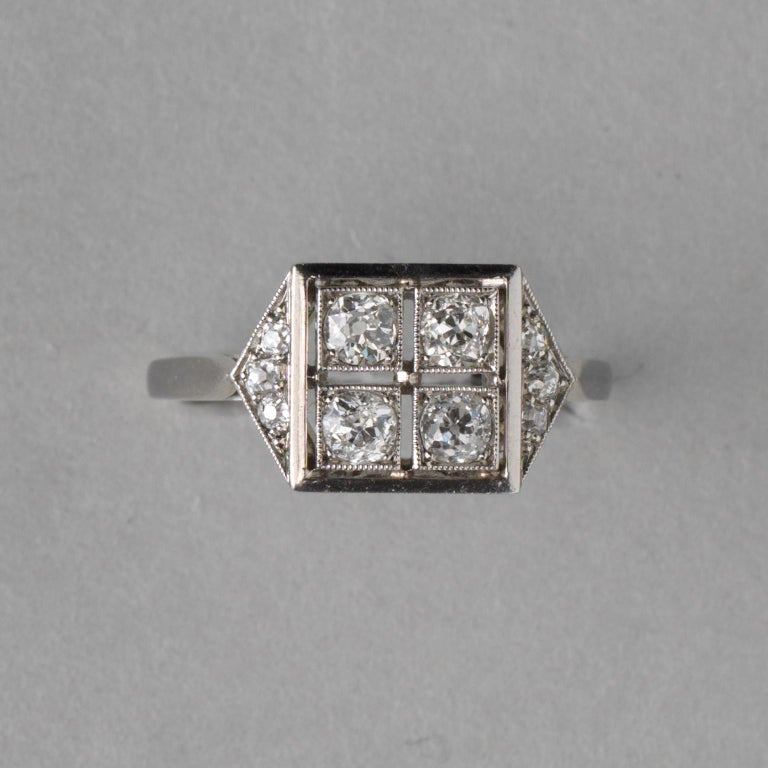 A platinum ring set with four old cut diamonds in a square each set in a mille griffe border with on each side a sloped triangle set with three diamonds (app. 0.7 carat), with a beautifully florally open worked gallery, numbered: 27500, France,