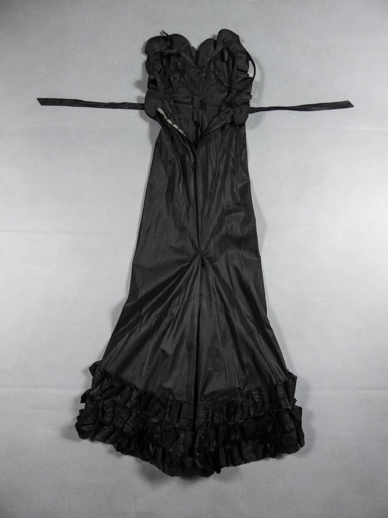 Circa 1935 France  Amazing evening dress with train in black silk taffetafrom a Parisian wardrobe mainly made up of Jean-Charles Worth Haute Couture Dress Circa 1935. Generous long dress with V-shaped backlessand thin straps. Buttoned at the back