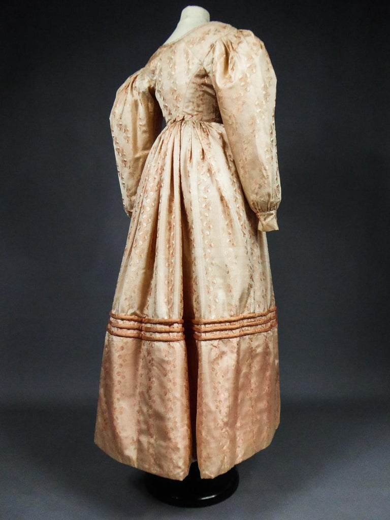 Circa 1825 France Charles X Period  Fashioned ball gown from the early Romantic silhouette period with its dropped shoulders and small mutton long sleeves. Light damask pale pink silk fabric with garlands of stylized flowers. High-waisted bodice,