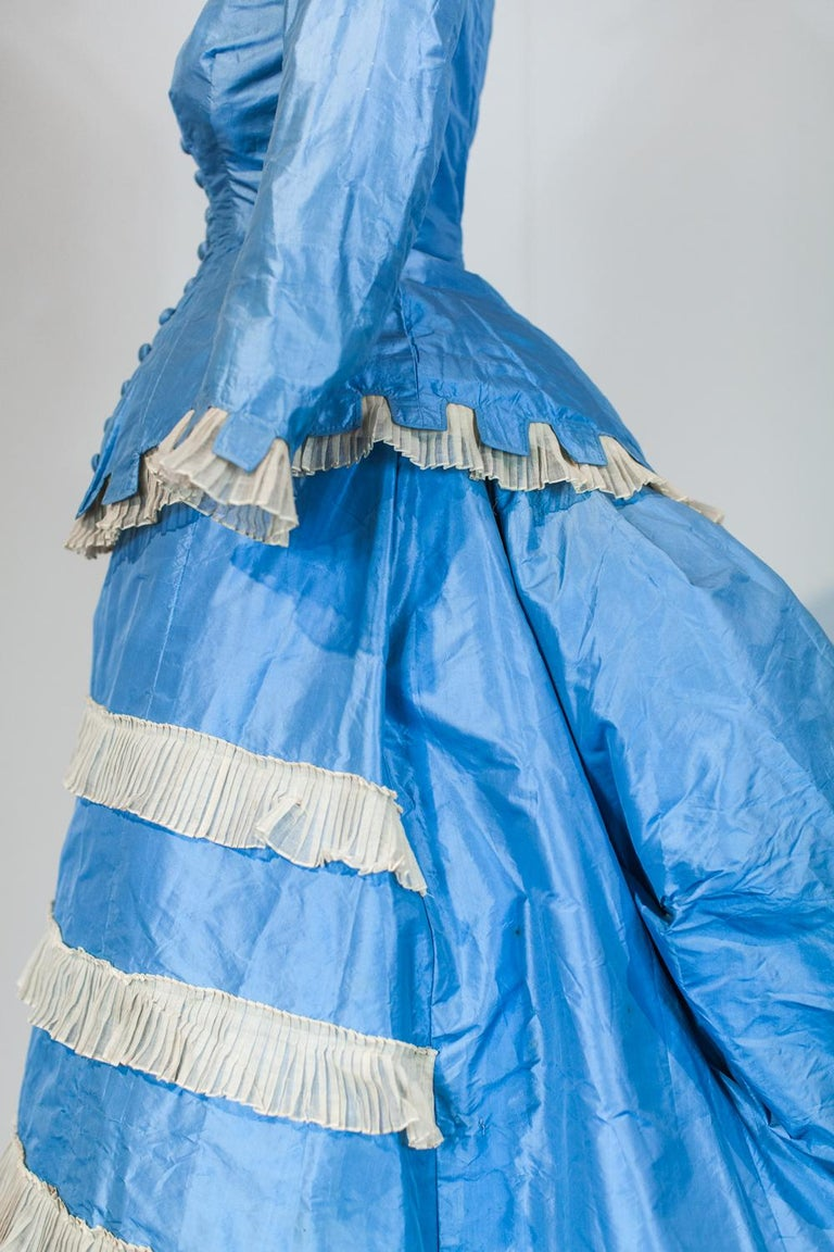 Circa 1870/1875 France.  Day dress with  princess, two-part bodice and skirt on a bustle cage. Sky-blue taffeta decorated with starched cream gauze called tarlatane, finely wrinkled and crenellated à la grecque. Boned bodice with long basque closing