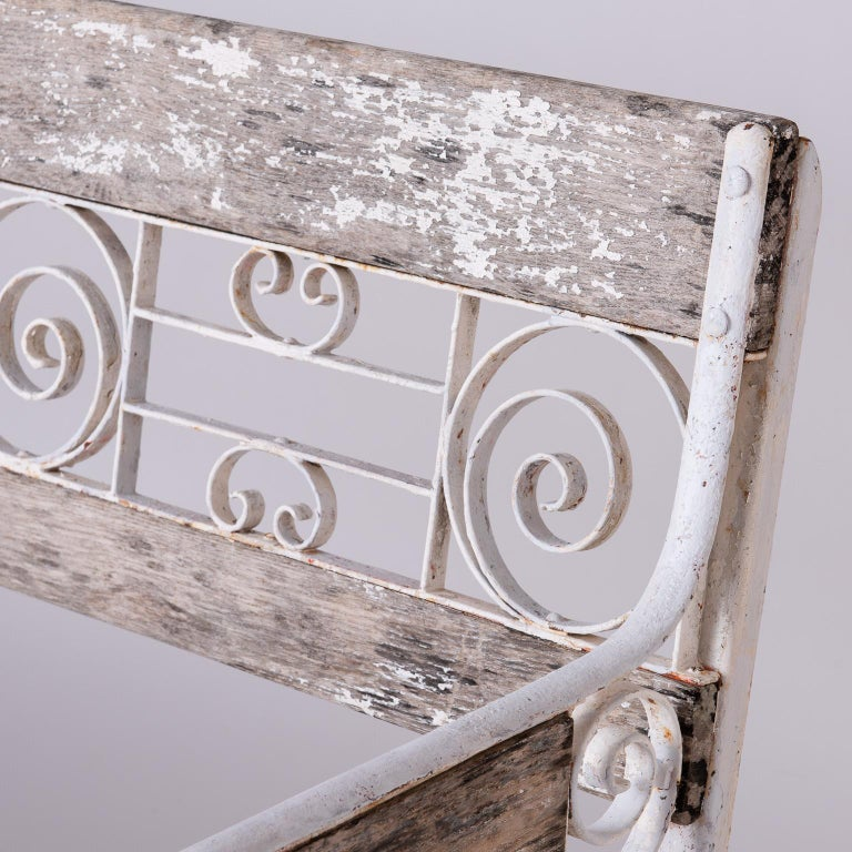 Featuring a classic combination of wood and wrought iron in a decorative pattern, this bench came from a hotel in Vichy, France, a town known for its luxurious spas and healing waters. The wood is nicely aged with traces of white paint remaining,