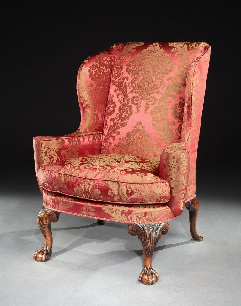 A particularly fine George I walnut wing chair, standing on acanthus carved cabriole legs terminating with ball and claw feet, the back legs well drawn and carved with scrolls.  This fine wing chair benefits from a great color and patina and