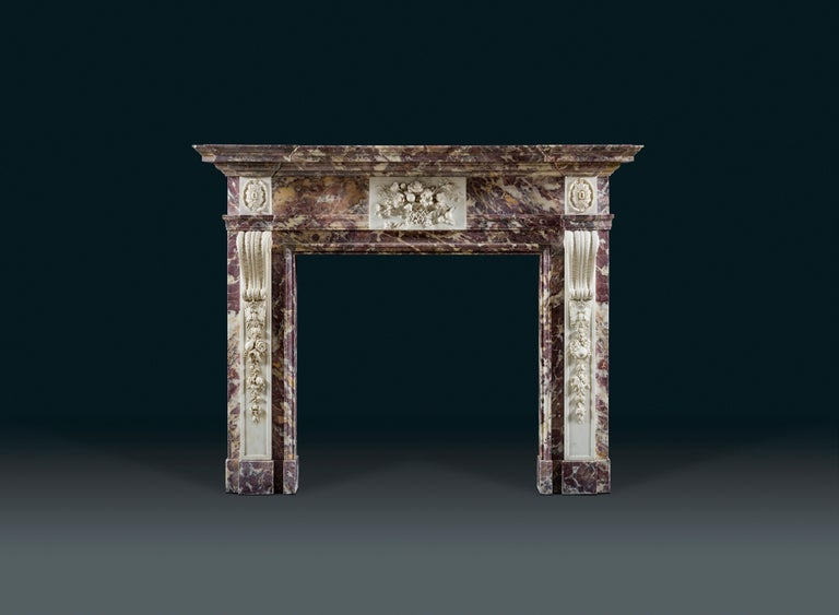 A rare and unusual George II, Palladian fireplace in variegated Breccia Violette marble decorated in contrasting statuary marble. The exceptionally fine naturalistically carved centre tablet bared a basket of fruits and flowers, attributes of spring
