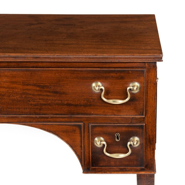 A George III free-standing mahogany architect's desk, the rectangular top above one long drawer fitted with an adjustable leathered reading slide with compartments underneath, and two small drawers in the spandrels, raised upon square tapering legs