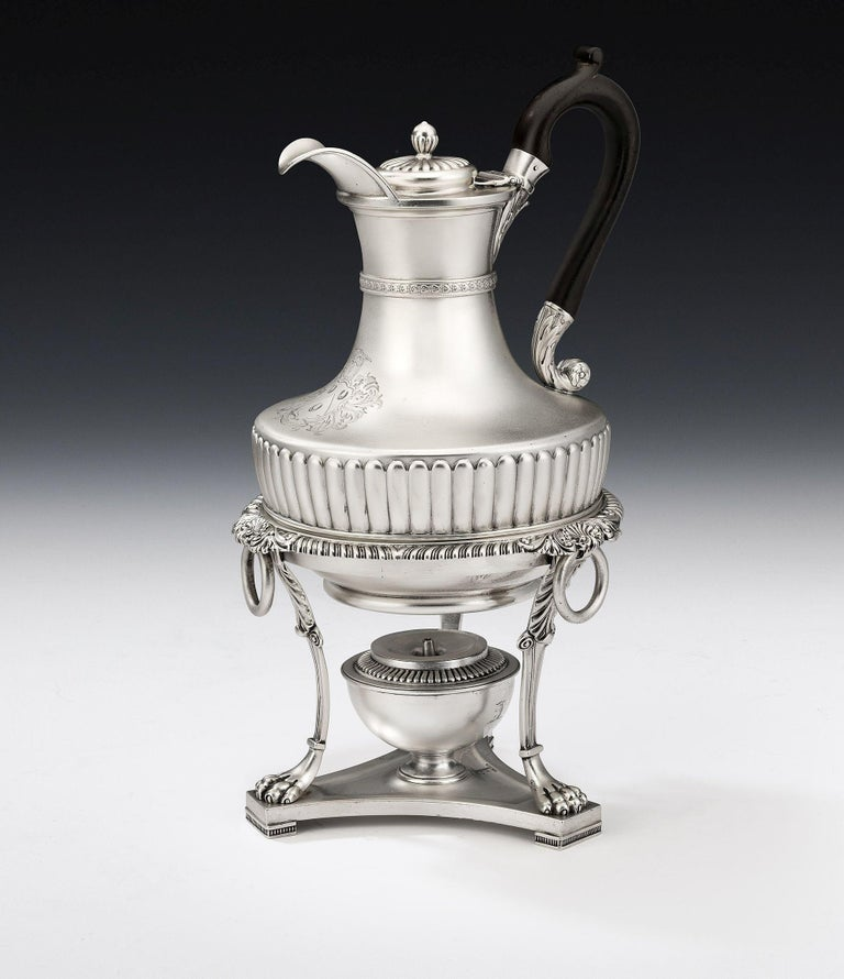 This important jug is modelled in the Regency Classical revival style. The main body has a pyriform body decorated with an unusual wide lobed band, which acts as a projecting ledge to support the jug on its Stand. A band of fruiting berries