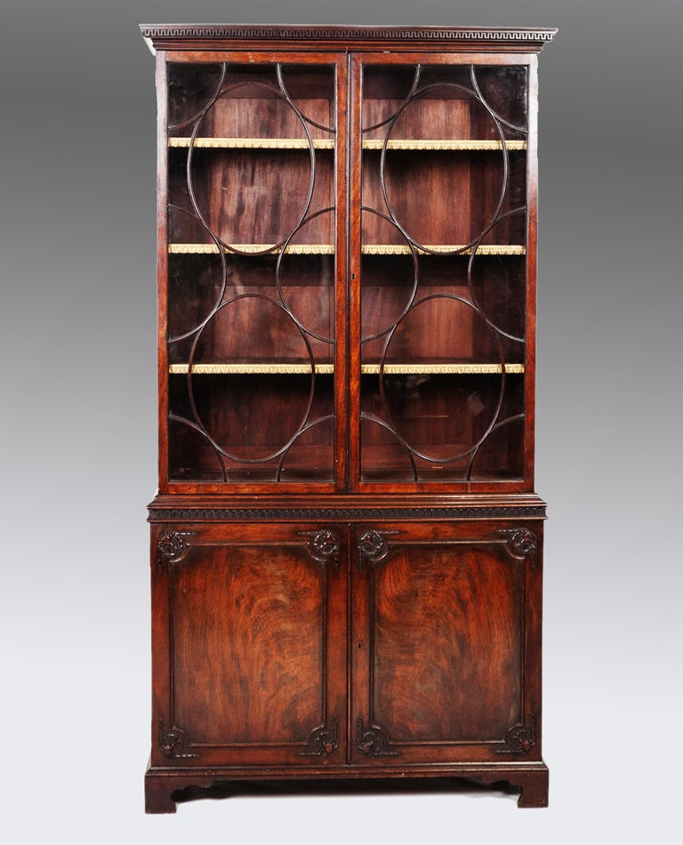 A George lll mahogany two-door bookcase. The well detailed moulded cornice with dental moulding, above arched glazed doors, resting on a two-door cabinet base, made from nicely figured mahogany, with raised panel mouldings and carved ram's heads in